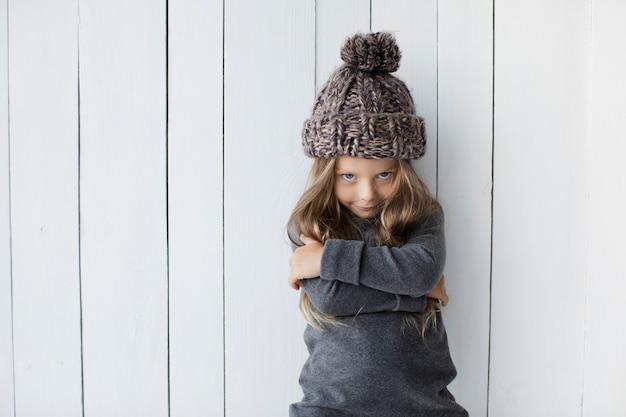 Blondes kleines mädchen, das in der winterkleidung aufwirft