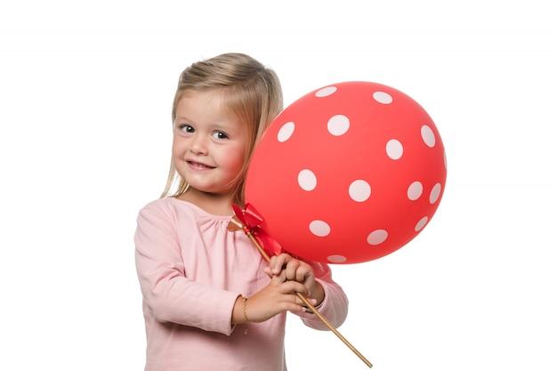 Blondes kleines mädchen, das zur kamera mit einem ballon lächelt