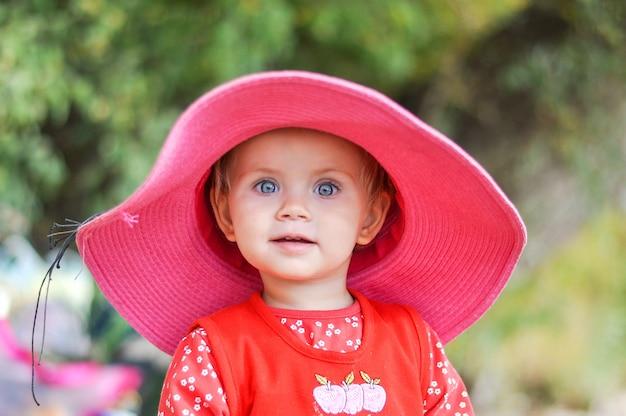 Blondes kleines mädchen im hut am strand in einem roten kleid im frühjahr