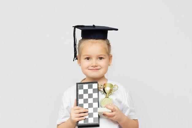 Blondes kleines mädchen im studentenhut mit dem schach- und goldbecher auf weißem hintergrundsieger