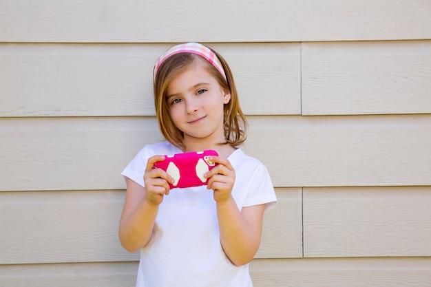 Blondes kleines mode-kindermädchen, das mit smartphone spielt
