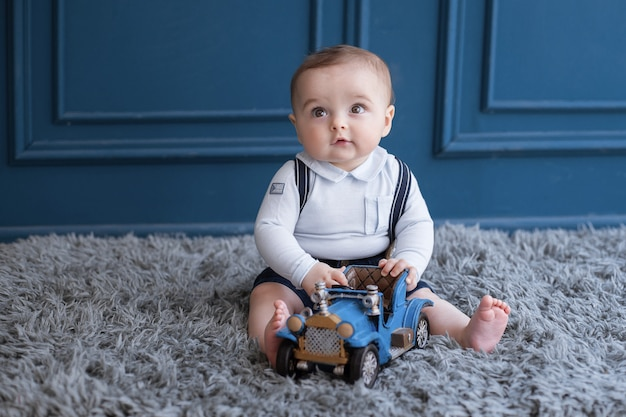 Blondes kleinkind, das auf einem teppich sitzt und mit einem blauen auto spielt.