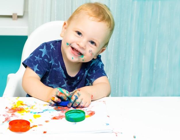 Blondes kleinkind, das mit fingerfarben zeichnet