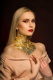Blondes luxusmodel mit hellem make-up und goldfolie am hals