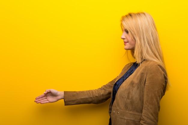 Blondes mädchen auf vibrierendem gelbem hintergrundhändeschütteln nach gutem geschäft