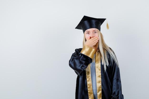 Blondes mädchen bedeckt den mund mit der hand in abschlusskleid und mütze und sieht überrascht aus