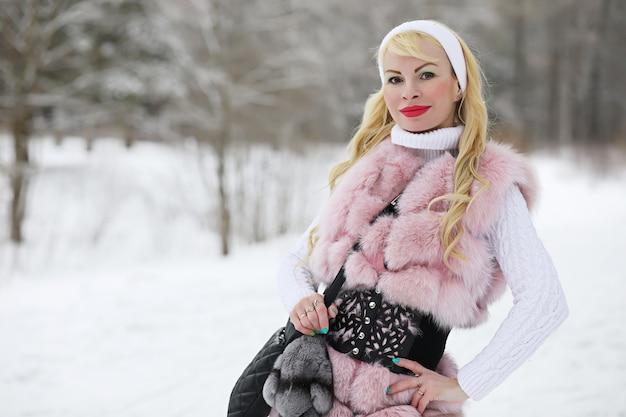 Blondes mädchen bei einem spaziergang in einem winterpark mit einem bewölkten tag