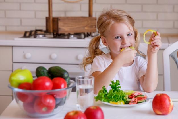 Blondes mädchen, das am tisch in der küche gemüse isst sitzt