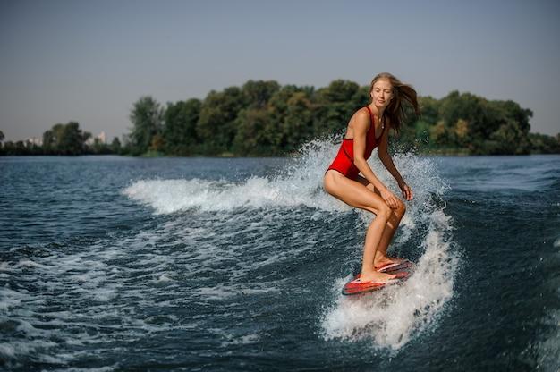 Blondes mädchen, das auf dem roten wakeboard steht
