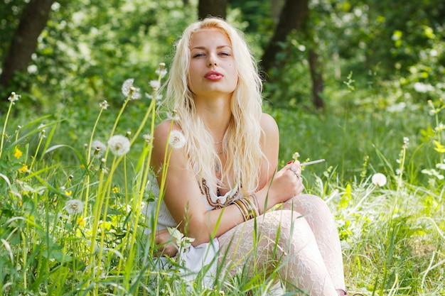 Blondes mädchen, das auf gras sitzt