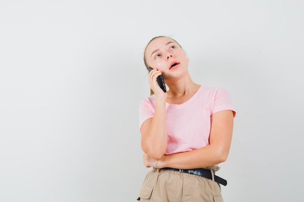 Blondes mädchen, das auf handy in t-shirt, hosen und nachdenklich schauen, vorderansicht spricht.