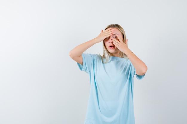 Blondes mädchen, das augen mit händen bedeckt, durch finger im blauen t-shirt schaut und hübsch, vorderansicht schaut.