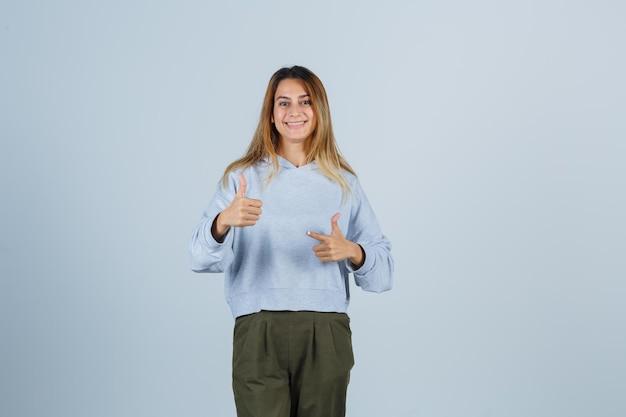Blondes mädchen, das daumen mit beiden händen in olivgrünem blauem sweatshirt und hosen zeigt und strahlend aussieht. vorderansicht.