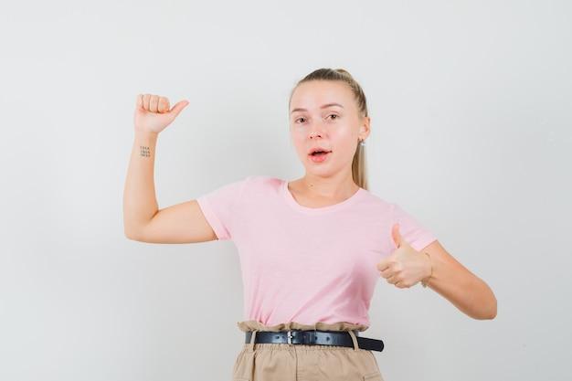 Blondes mädchen, das daumen oben zeigt, arm im t-shirt, in der hose hebt und selbstbewusst aussieht. vorderansicht.