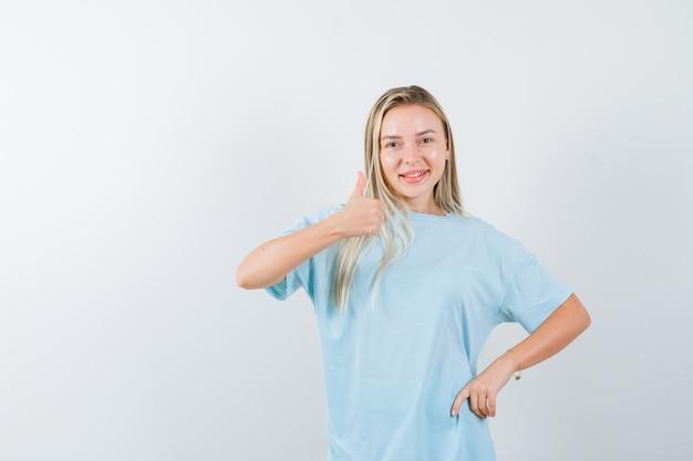 Blondes mädchen, das daumen oben zeigt, hand auf taille im blauen t-shirt haltend und selbstbewusst, vorderansicht schauend.