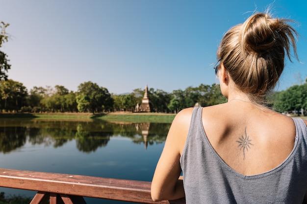 Blondes mädchen, das den see in der natur im park von sukhotai in thailand betrachtet.