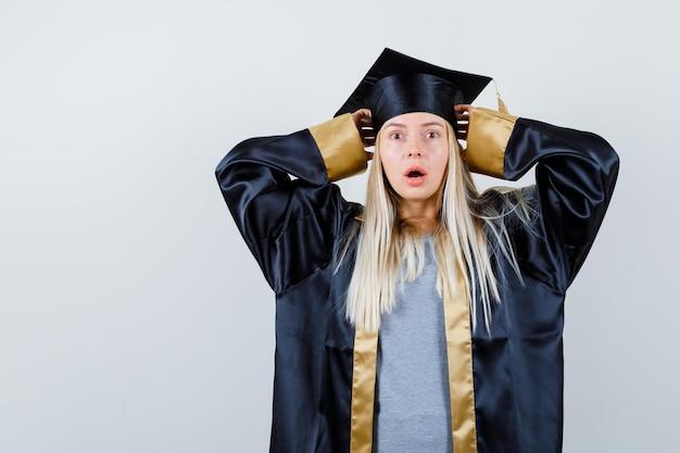 Blondes mädchen, das die hände an der mütze mit weit geöffnetem mund in abschlusskleid und mütze hält und überrascht aussieht.