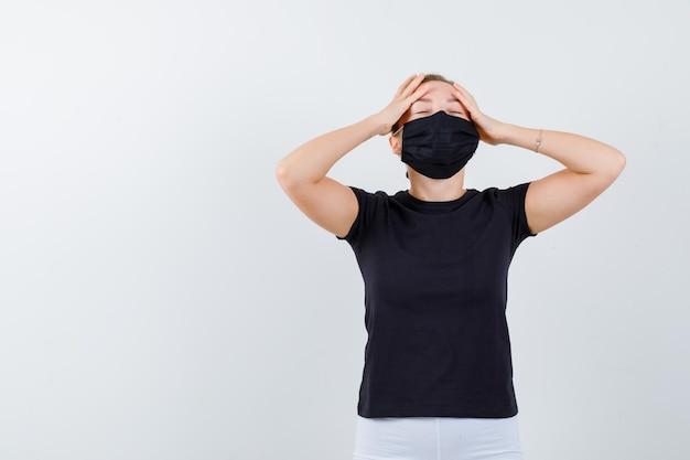 Blondes mädchen, das die hände auf der stirn im schwarzen t-shirt hält, isoliert