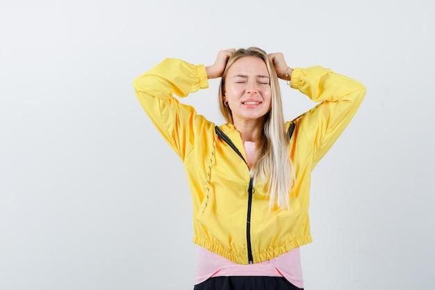 Blondes mädchen, das die hände in der gelben jacke am kopf hält und vergesslich aussieht