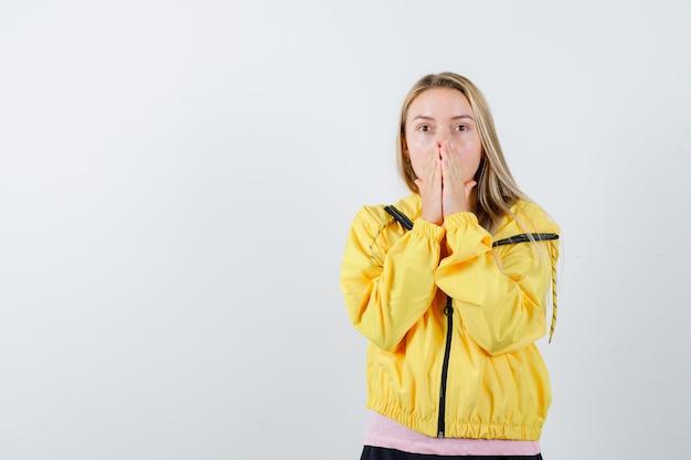 Blondes mädchen, das die hände in der gelben jacke am mund hält und verängstigt aussieht