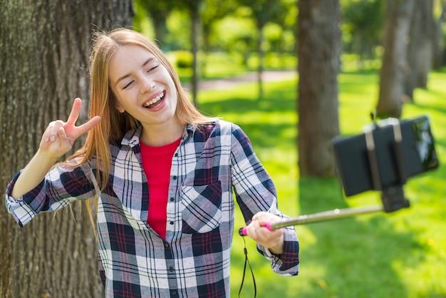 Blondes mädchen, das ein selfie nahe bei einem baum nimmt