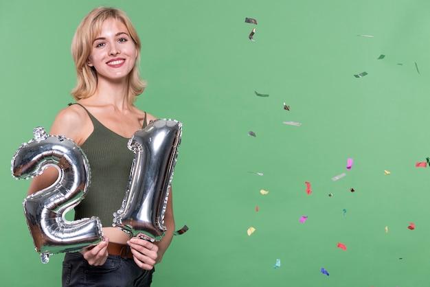 Blondes mädchen, das ein zeichen mit 21 ballonen anhält