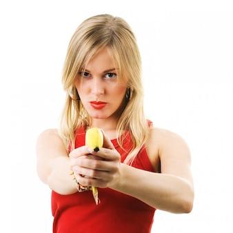 Blondes mädchen, das eine banane vortäuscht, ist eine gewehr