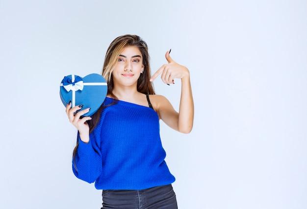 Blondes mädchen, das eine blaue herzform-geschenkbox hält.