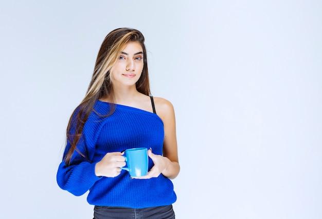 Blondes mädchen, das eine blaue kaffeetasse hält.