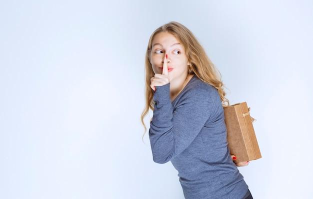 Blondes mädchen, das eine geschenkbox aus karton hinter sich versteckt.