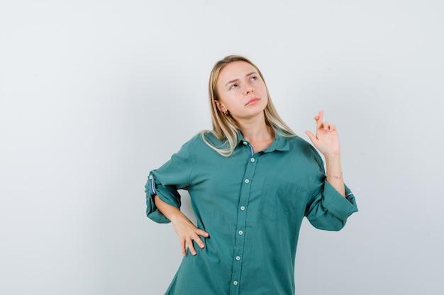 Blondes mädchen, das eine hand an der taille hält, während es die finger in der grünen bluse gekreuzt hält und nachdenklich aussieht