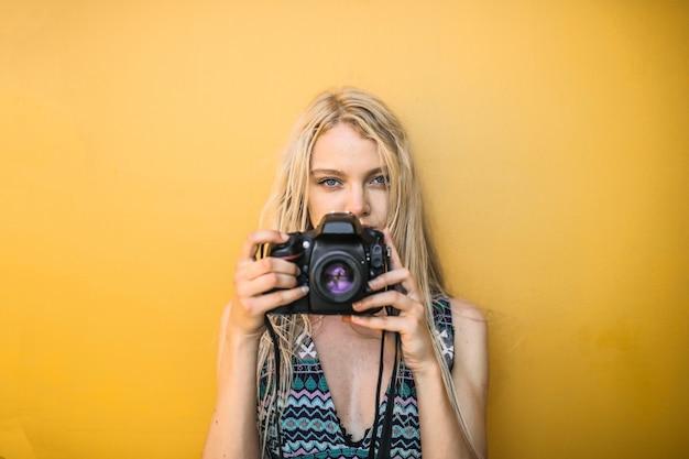 Blondes mädchen, das eine kamera anhält