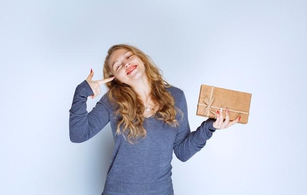 Blondes mädchen, das eine pappgeschenkbox hält und eine idee hat.