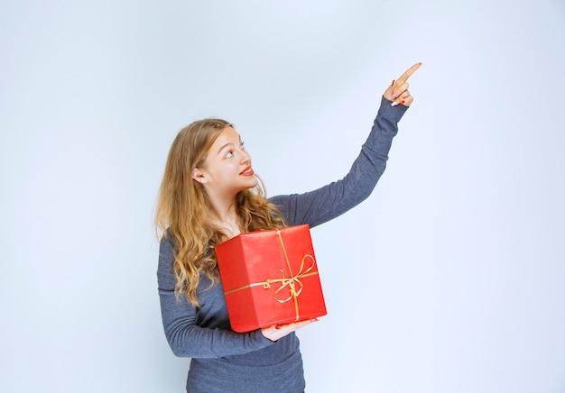 Blondes mädchen, das eine rote geschenkbox hält und jemand zeigt.