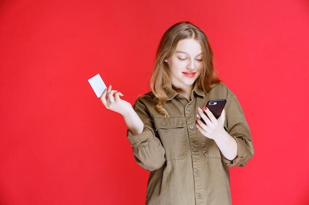 Blondes mädchen, das eine visitenkarte hält und mit dem telefon spricht.