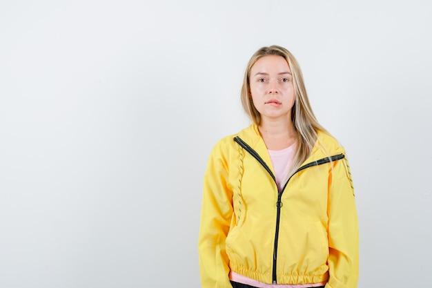 Blondes mädchen, das gerade steht, lippen beißt und in der kamera im rosa t-shirt und in der gelben jacke aufwirft und verführerisch schaut