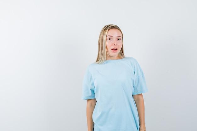 Blondes mädchen, das gerade steht und an der kamera im blauen t-shirt aufwirft und hübsch schaut, vorderansicht.