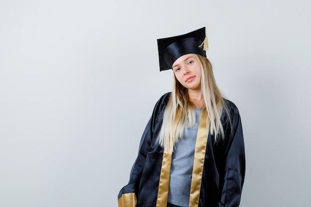 Blondes mädchen, das gerade steht und in abschlusskleid und mütze vor der kamera posiert und süß aussieht