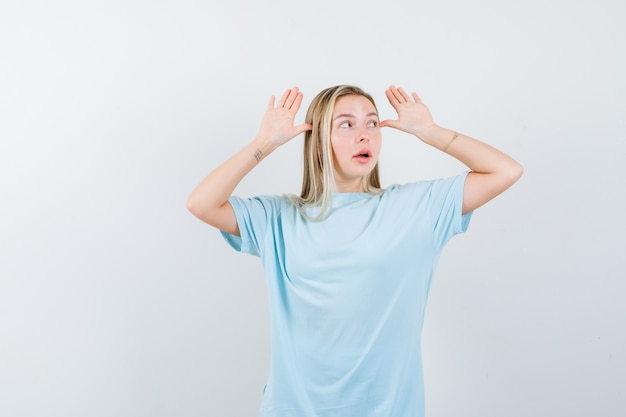 Blondes mädchen, das hände nahe kopf hält, weg im blauen t-shirt schaut und niedlich schaut. vorderansicht.