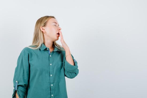 Blondes mädchen, das hand auf den mund legt, in grüner bluse gähnt und schläfrig aussieht looking