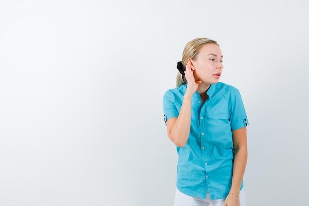 Blondes mädchen, das hand hinter dem ohr hält, um in blauer bluse zu hören, weiße hose isoliert