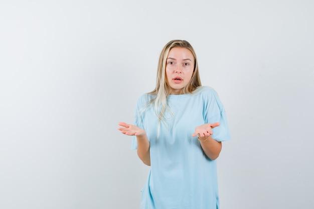 Blondes mädchen, das hilflose geste im blauen t-shirt zeigt und verwirrt schaut. vorderansicht.