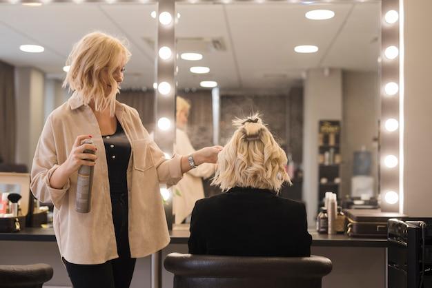 Blondes mädchen, das ihr haar erledigt erhält
