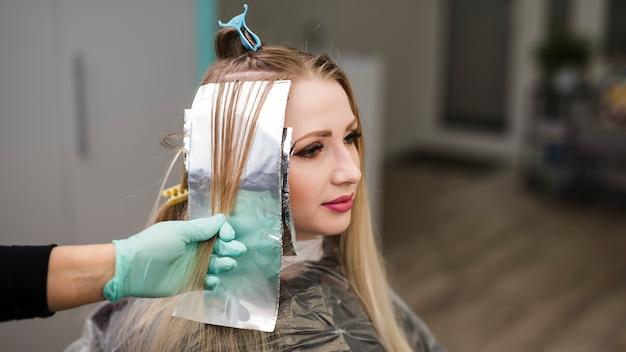 Blondes mädchen, das ihre haarfärbung erhält