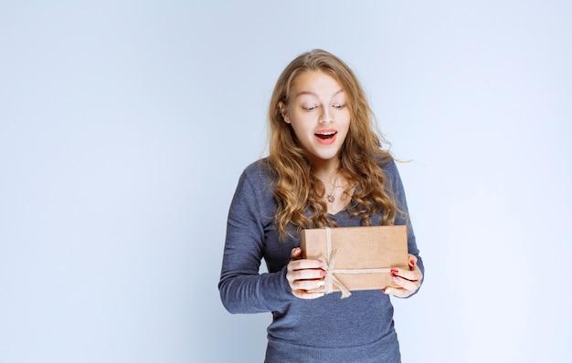 Blondes mädchen, das ihre pappgeschenkbox demonstriert und sich positiv fühlt.