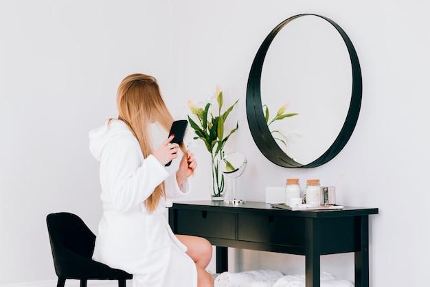 Blondes mädchen, das ihre reflexion betrachtet