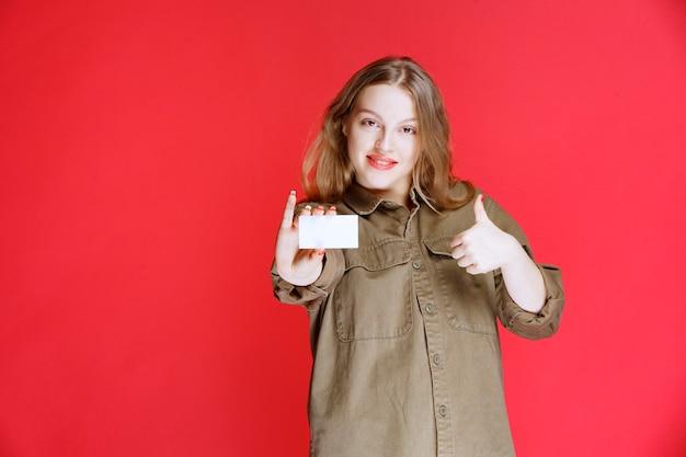 Blondes mädchen, das ihre visitenkarte und positives handzeichen zeigt.