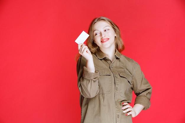 Blondes mädchen, das ihre visitenkarte und vernetzung zeigt.