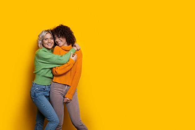 Blondes mädchen, das ihren kaukasischen lockigen freund umarmt, während auf einem gelben hintergrund mit etwas freiraum posiert