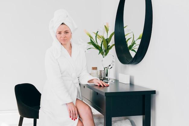 Blondes mädchen, das im badezimmer mit bademantel aufwirft